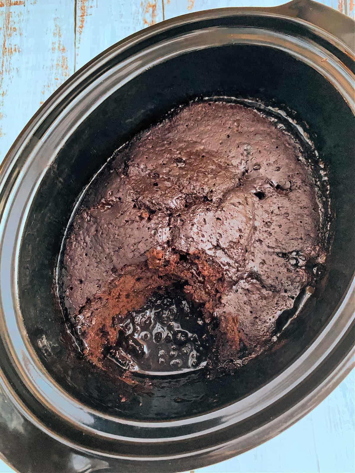 Chocolate sponge pudding with chocolate sauce in slow cooker pot, one portion removed to show the sauce.