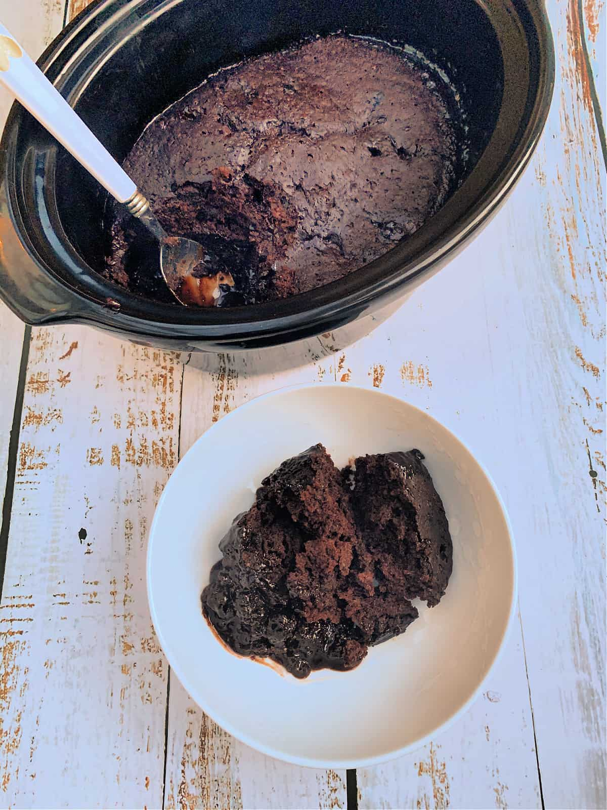 A slow cooker with chocolate lava cake and a spoon, and a bowl of the dessert in front of it.