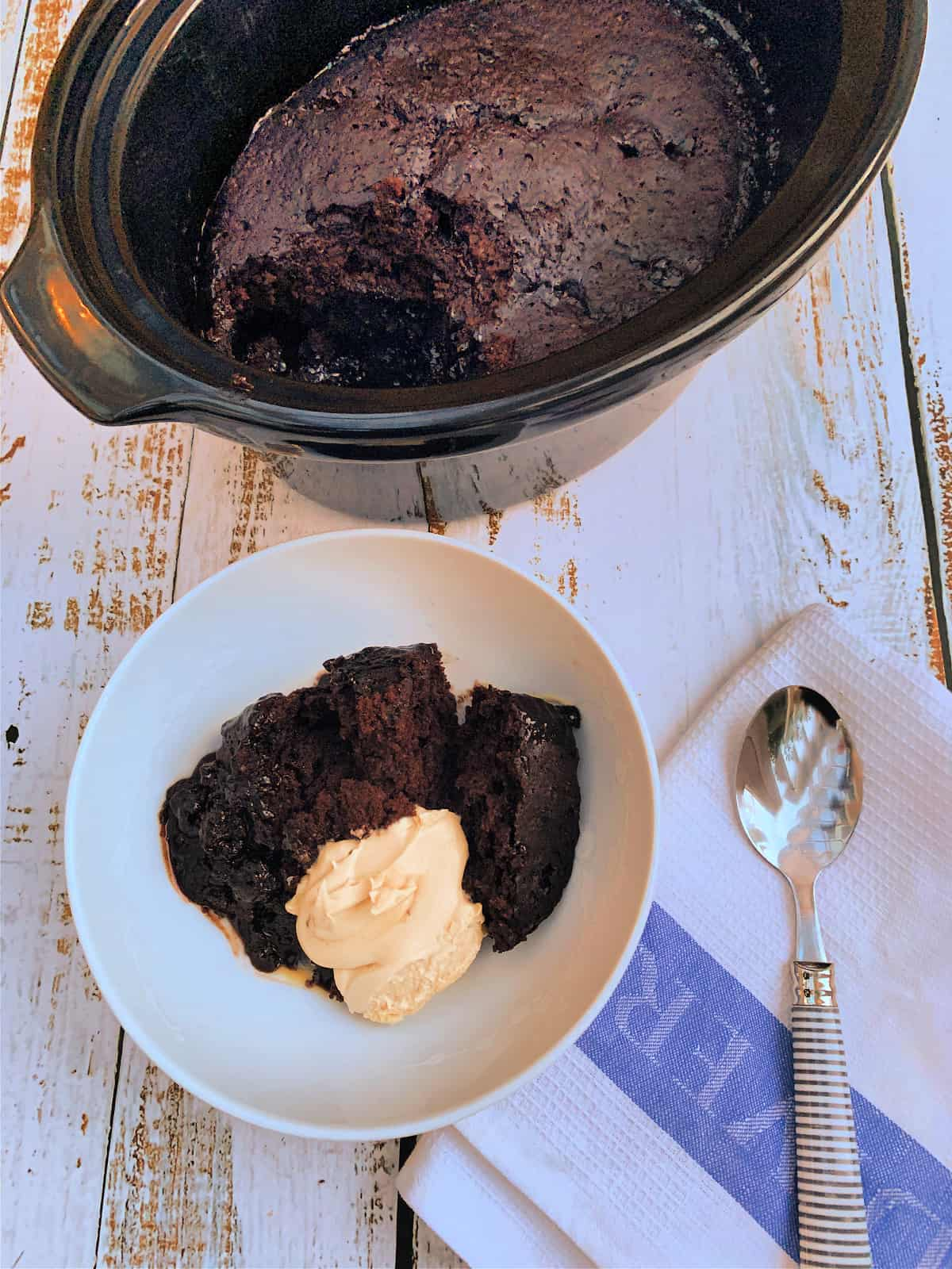 Slow cooker in background, bowl of chocolate lava cake with cream in front, with a spoon to the side.