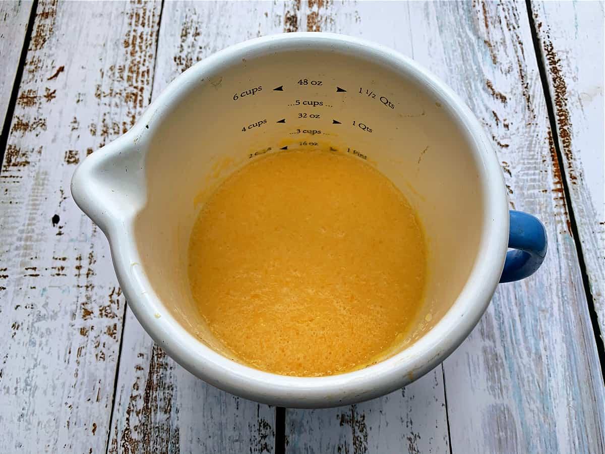 Jug of milk, melted butter, eggs and orange juice.