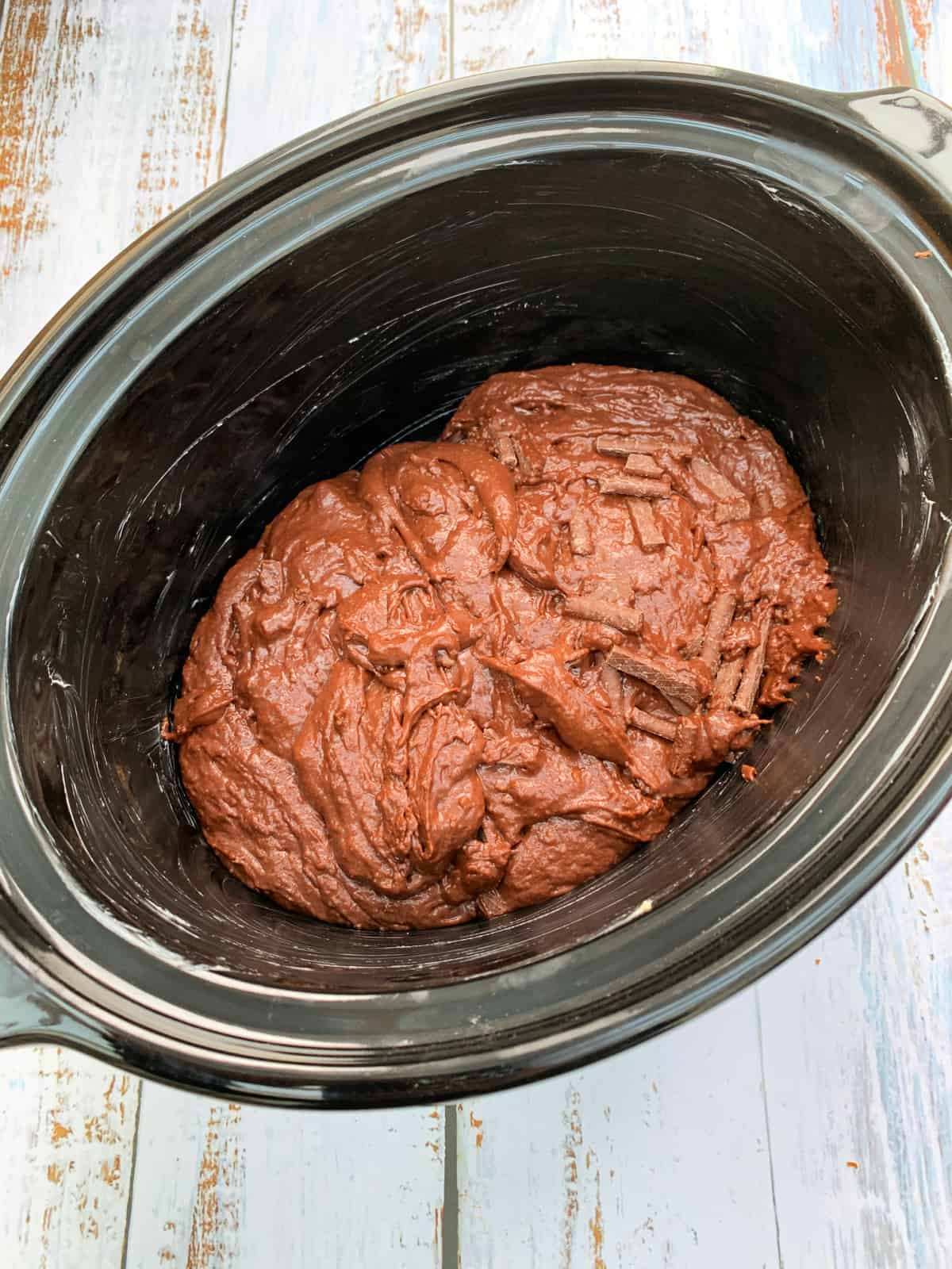 Slow cooker pot with chocolate cake mixture in it.