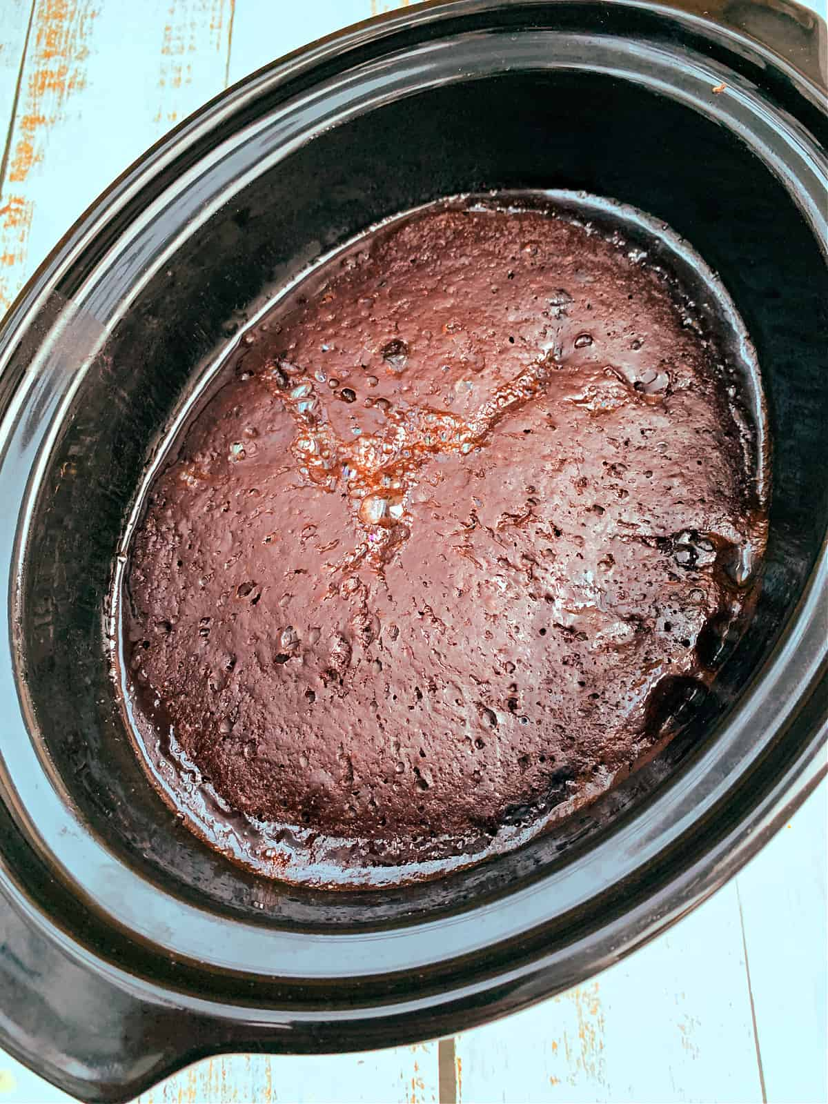 Chocolate orange pudding after baking, with a rich chocolate sponge cake layer over a chocolate sauce.