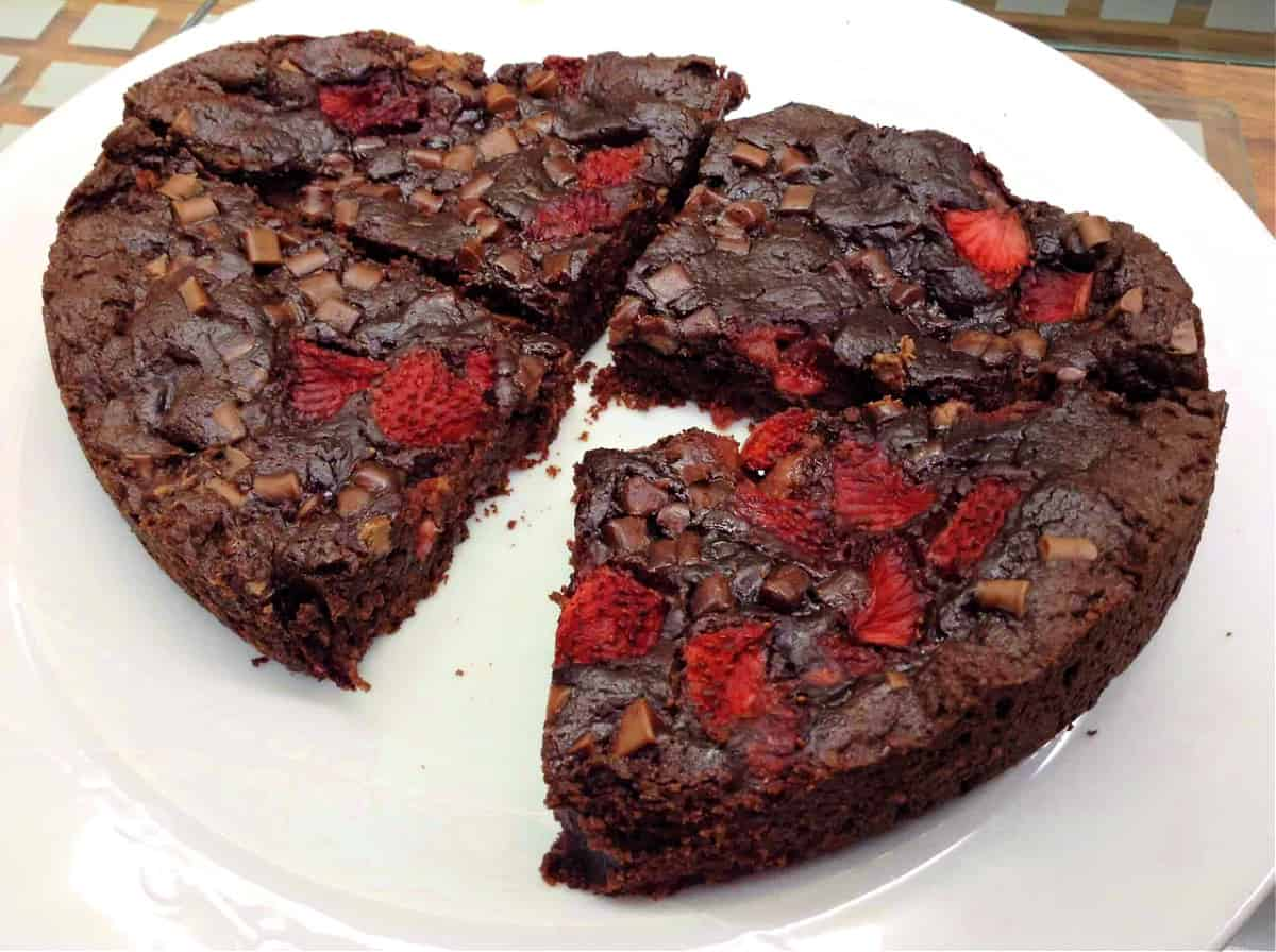 Double chocolate cookie with strawberries on a white plate, cut into 4.
