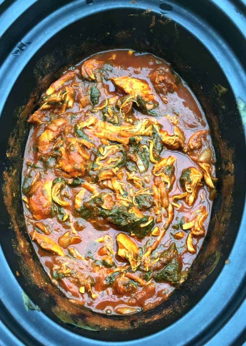 Overhead photo of chicken and spinach curry in slow cooker pot.