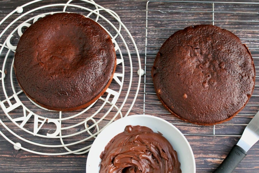 Two cakes on a rack and a bowl of chocolate ganache.
