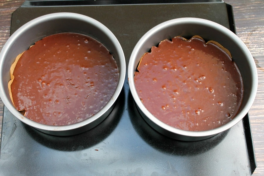 Two baking tins filled with chocolate cake mixture, ready to bake.