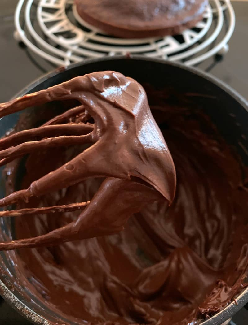 Chocolate ganache icing on a whisk.