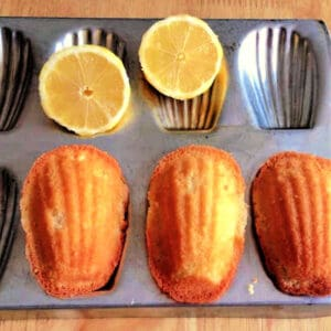 Madeleine cakes in a madeleine tin, with lemon halves.