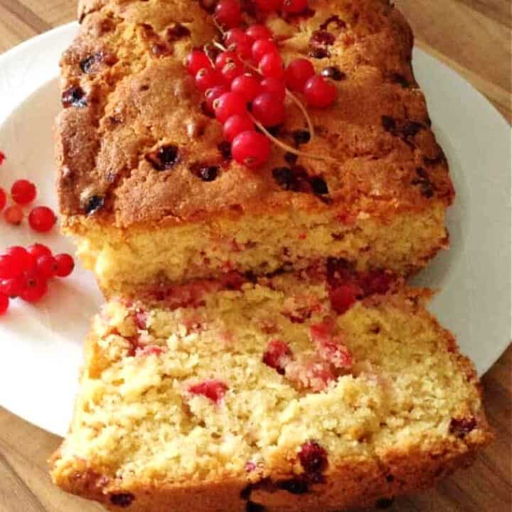 Close up of a sliced redcurrant loaf cake, showing the fruit inside.