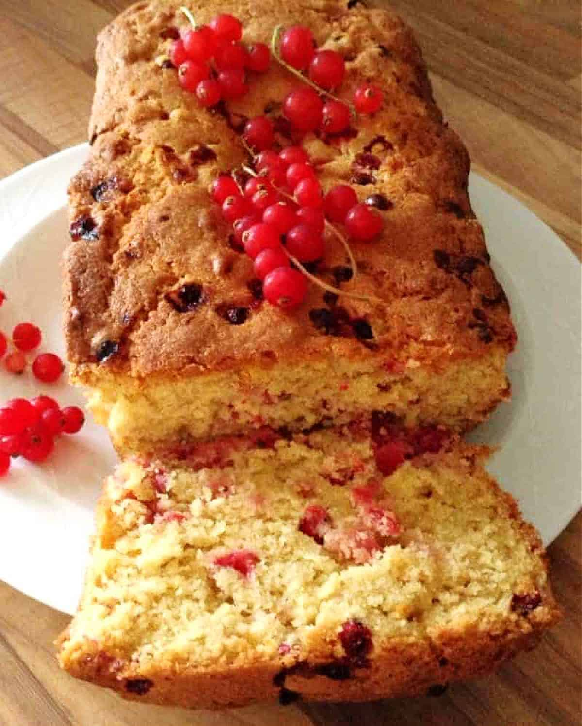 A loaf cake filled with redcurrant cut open on a white plate.