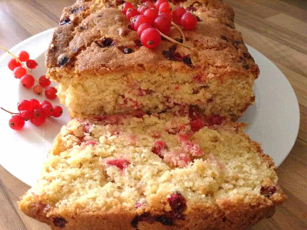 horizontal shot of loaf cake on plate with redcurrants next to it.