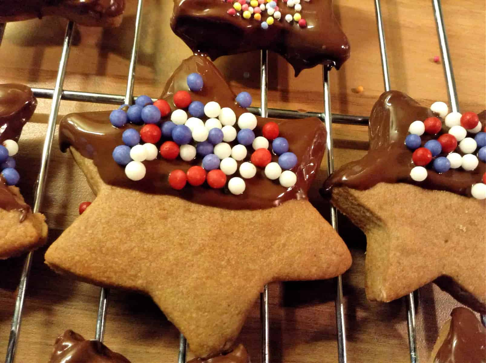 Close up of star shaped chocolate cookies with half chocolate covering and sprinkle decoration.