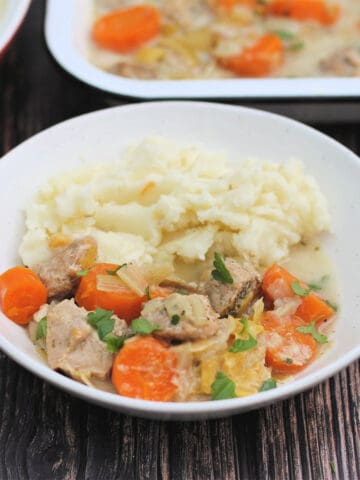 Close up of white bowl of pork casserole with carrots and mash.