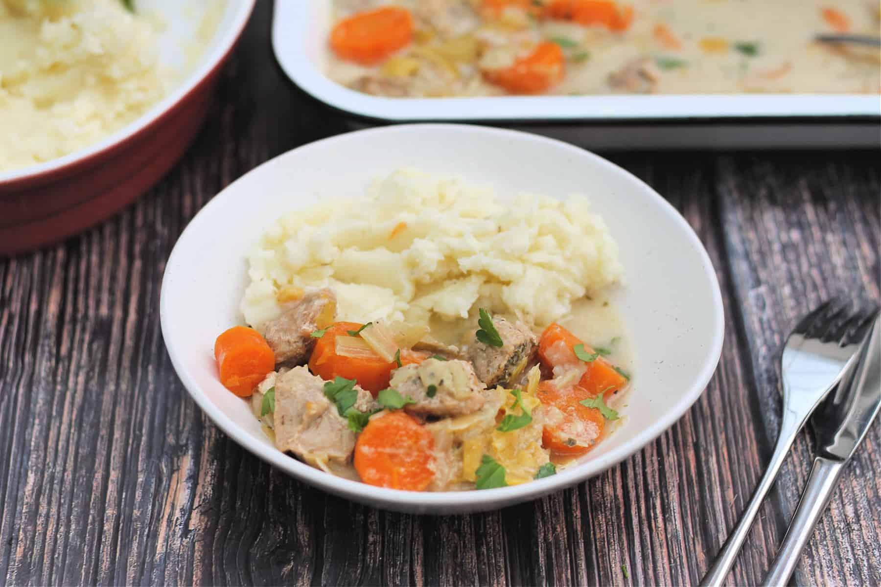 Bowl of pork casserole with cutlery beside.