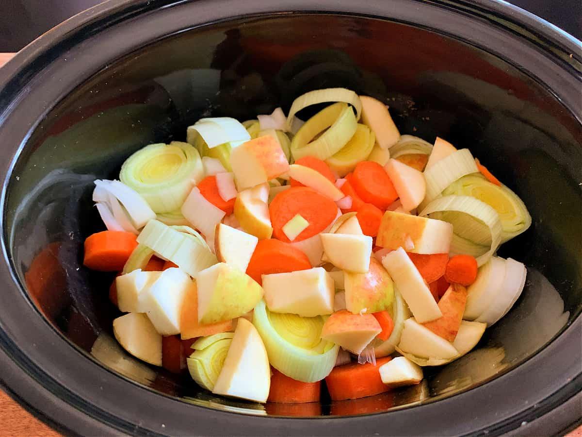 Sliced vegetables in slow cooker pot.