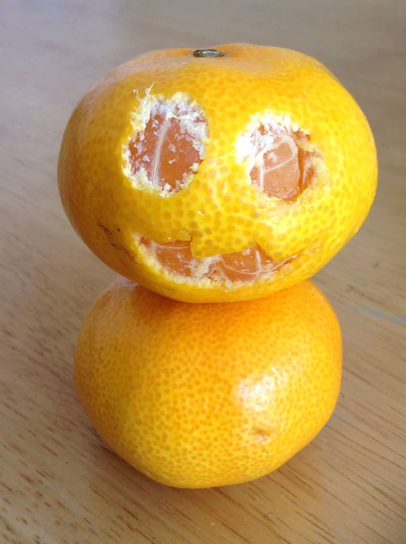 Satsuma with a scary pumpkin face cut out of the skin.
