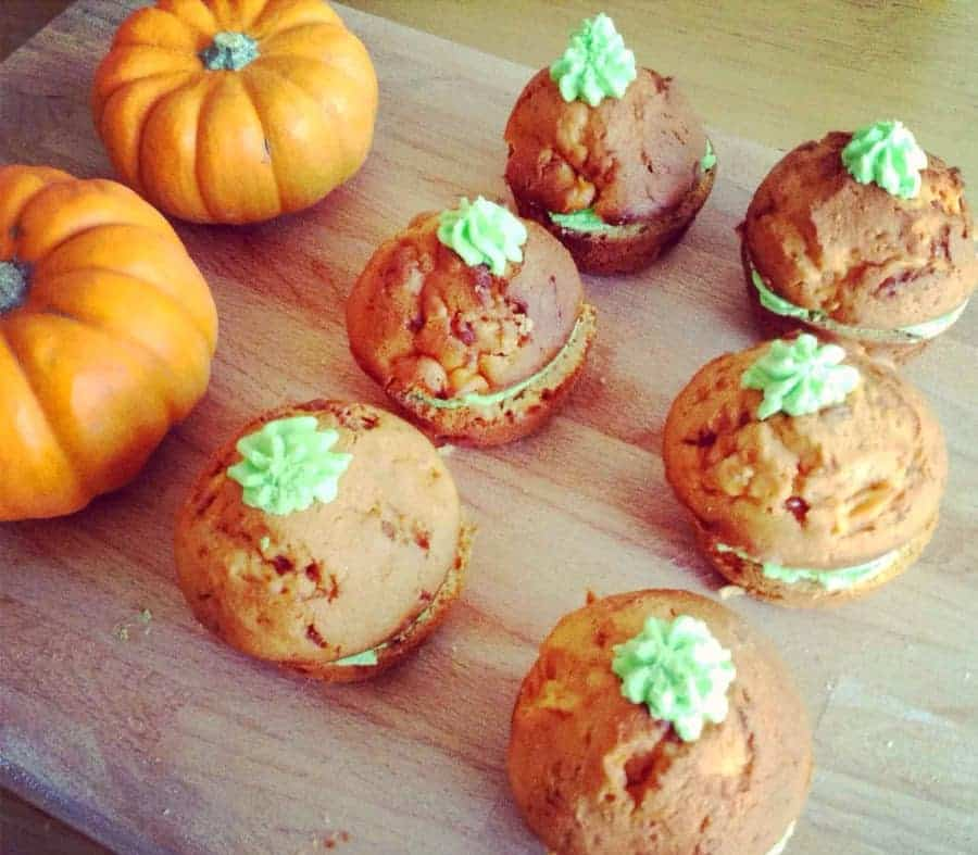 Orange cakes with green icing like pumpkins.