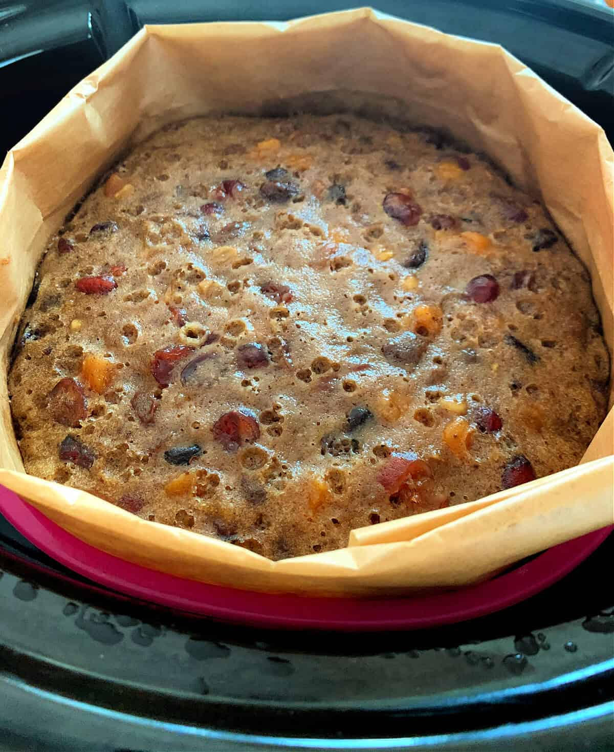 Christmas Cake in lined silicone pan in slow cooker, after baking.