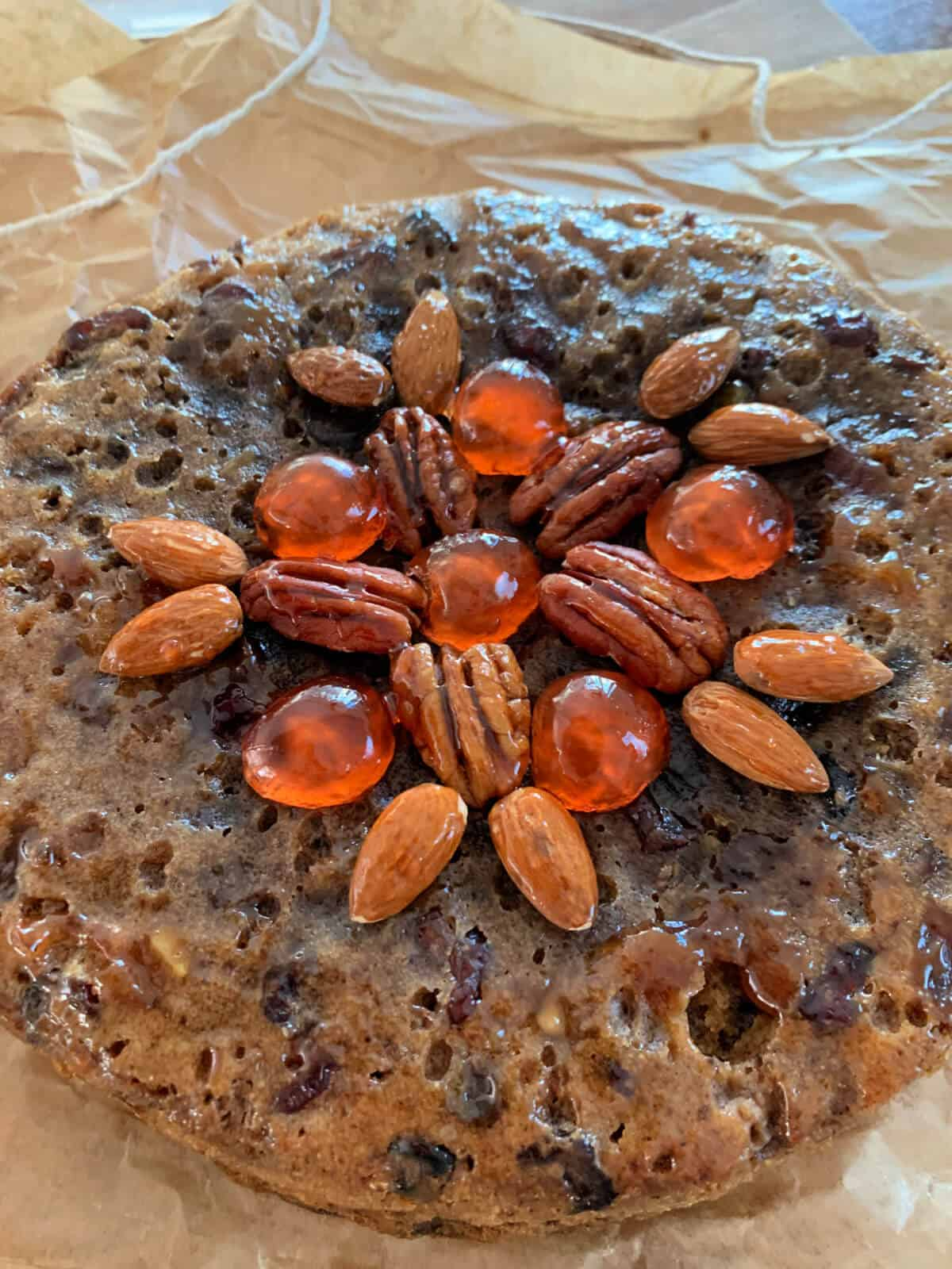 Close up of top of fruit cake decorated with nuts and cherries.