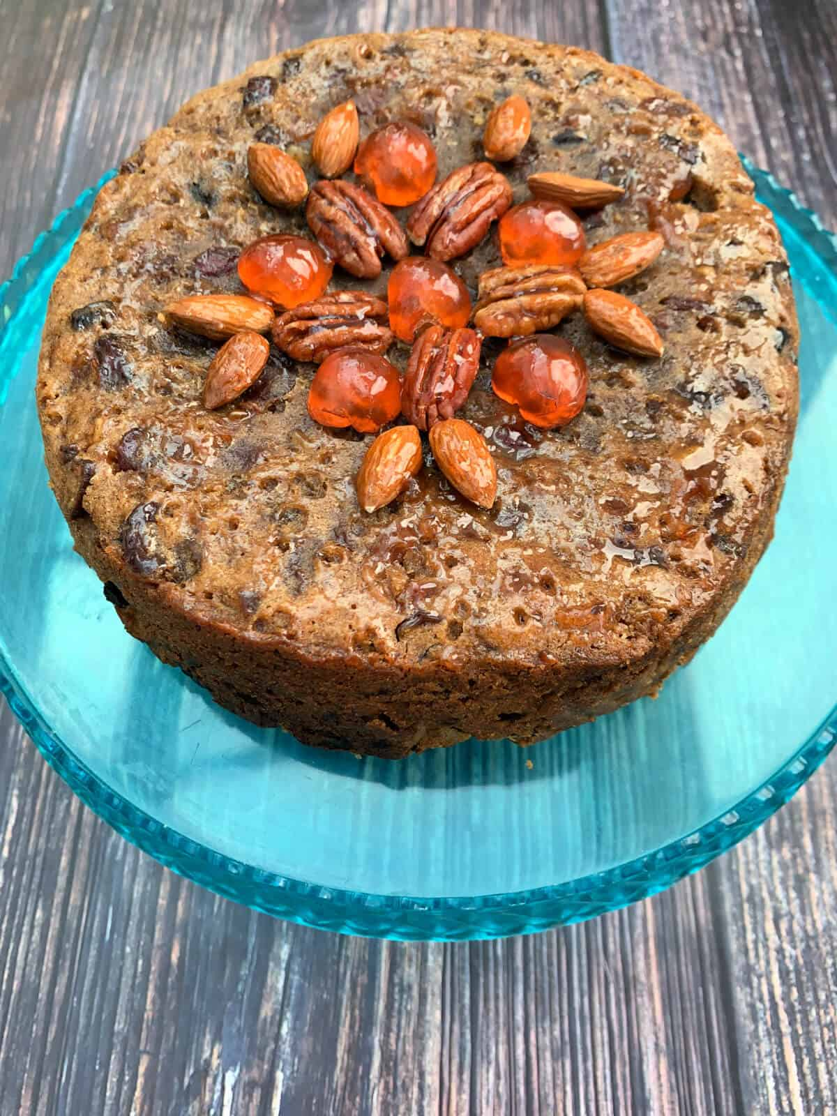 Christmas fruit cake decorated with fruit and nuts on a blue cake stand.