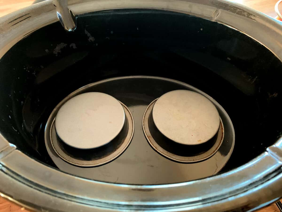 Slow cooker pot with two small upturned cake tins at the base.