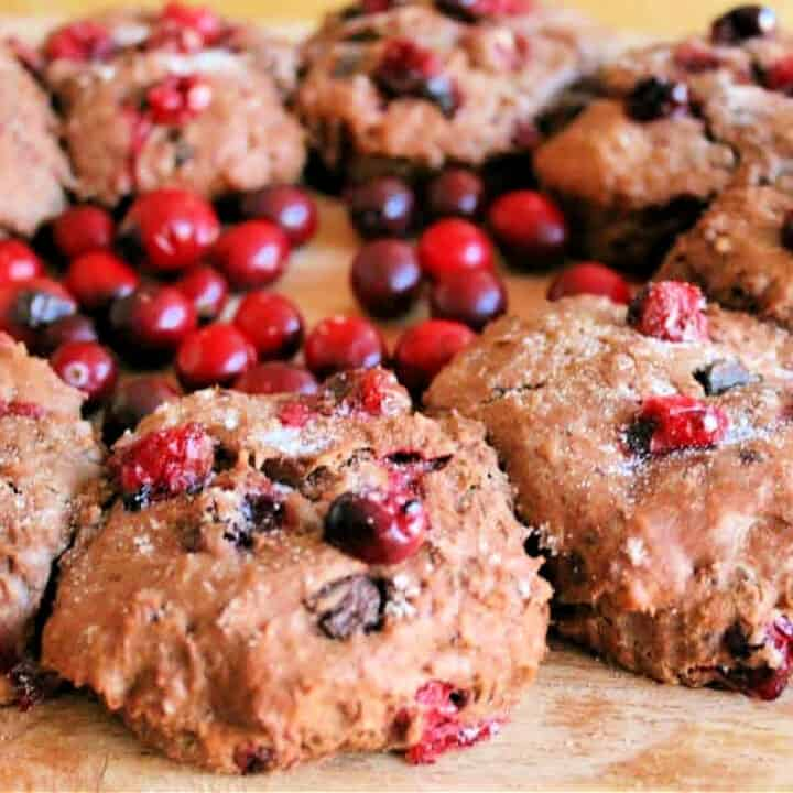 Chocolate scones with cranberries on a wooden board, with fresh cranberries.