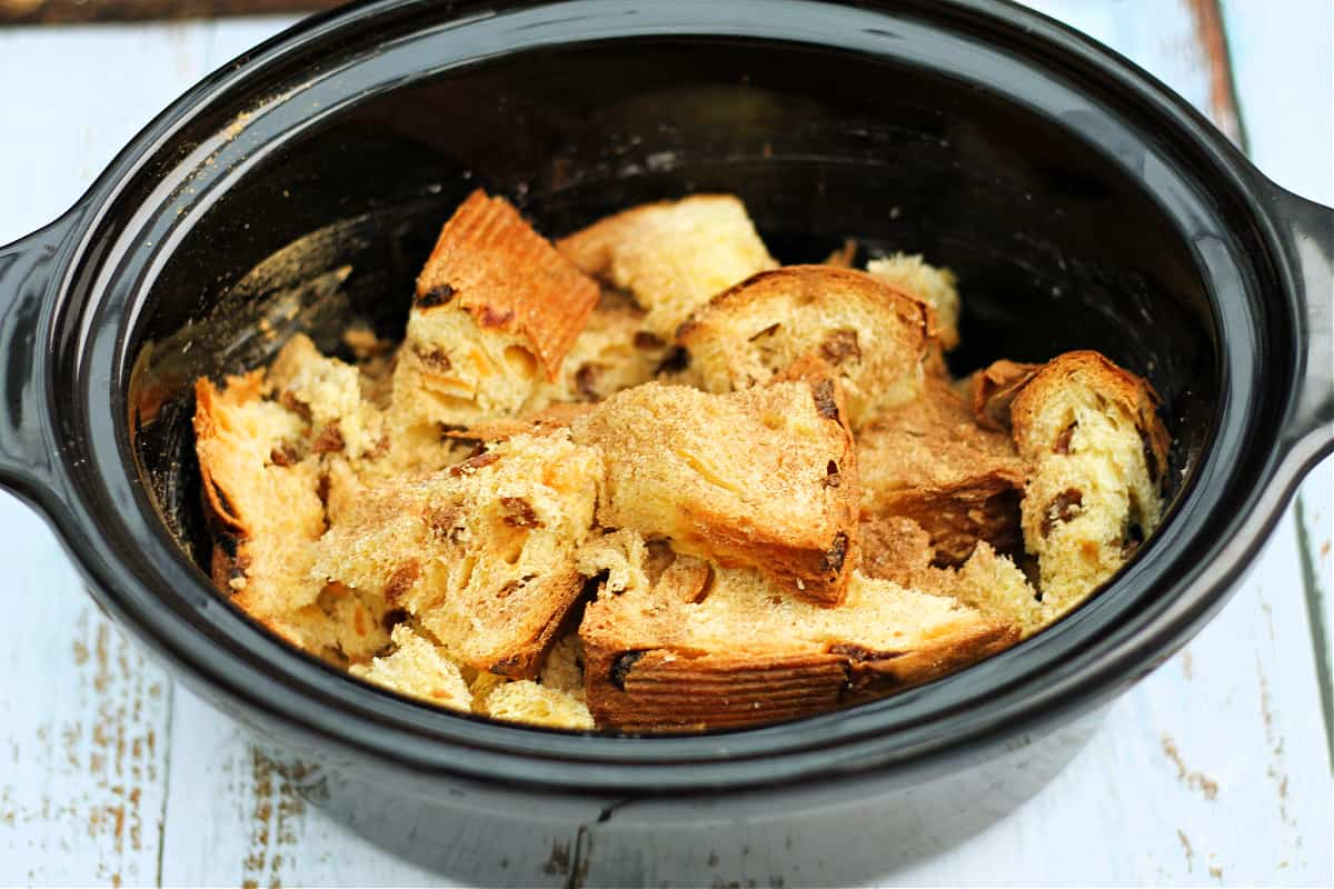 Two layers of panettone in slow cooker pot, with spices sprinkled over.