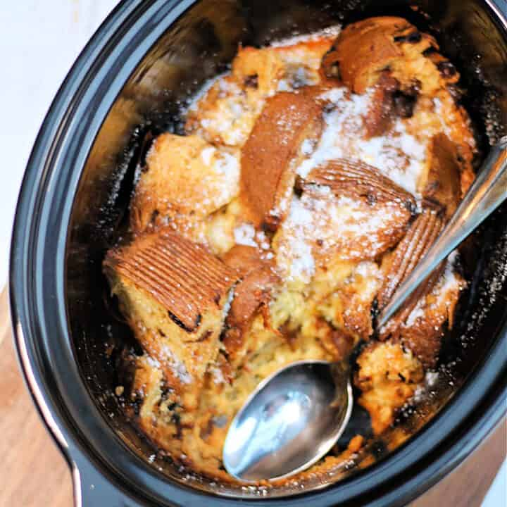 Panettone pudding in slow cooker pot with serving spoon.