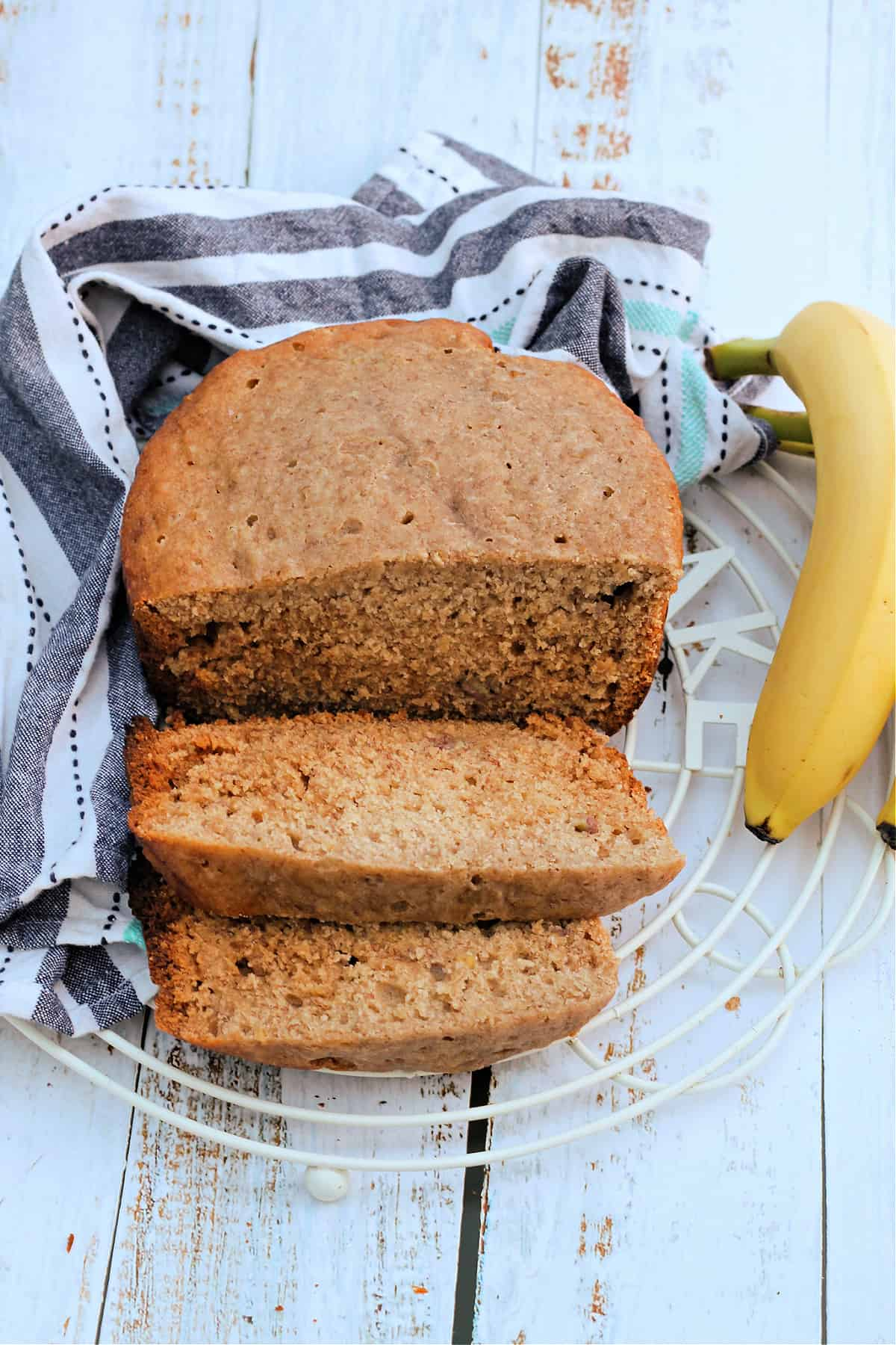 Banana bread on rack with two slices cut out, with bananas and a cloth behind.