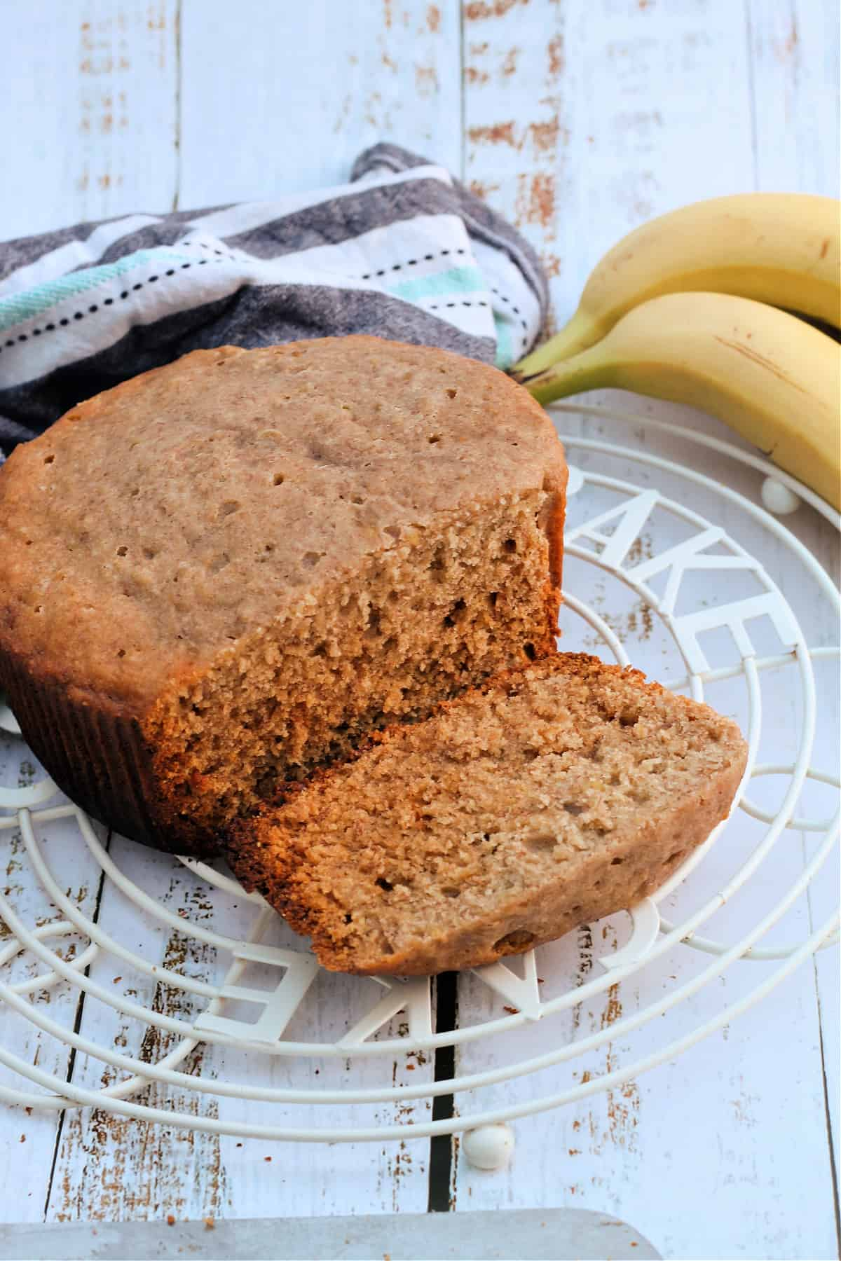 Banana bread on a cooling rack, one slice cut ready to eat.