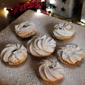 Close up of mince pies dusted with icing sugar on a wooden board.