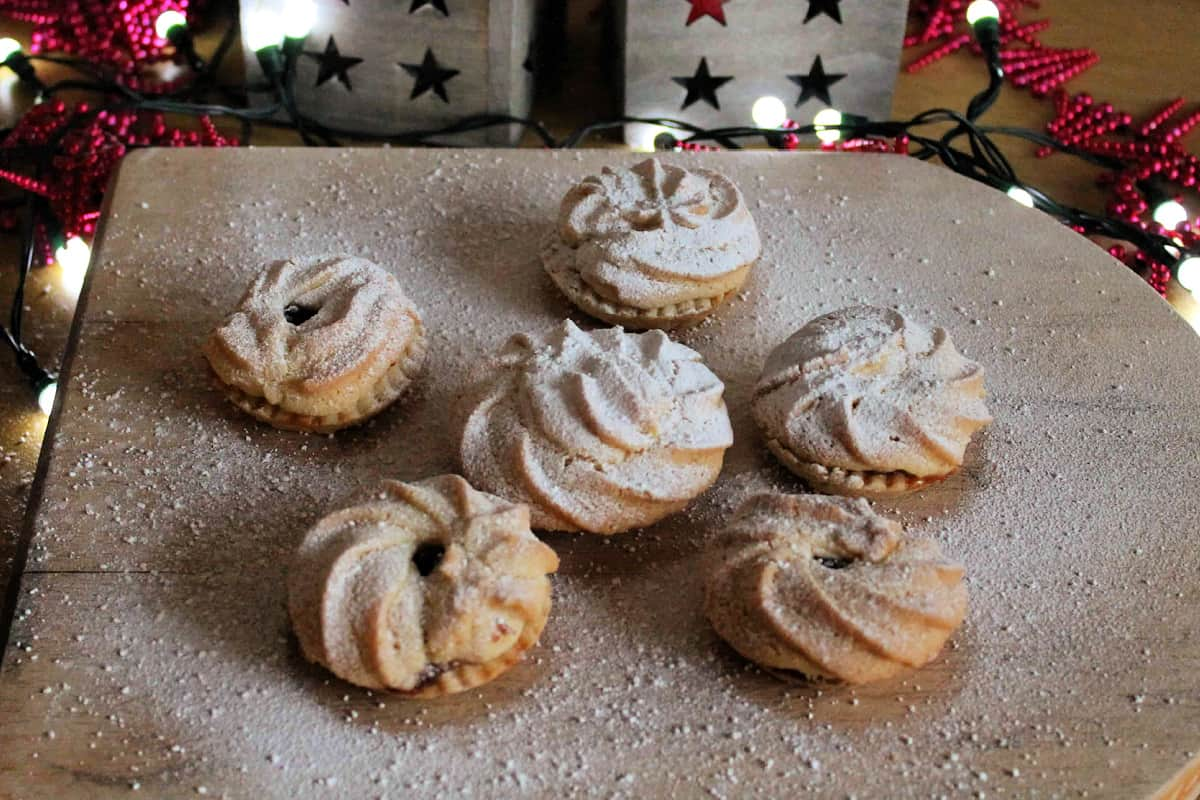 Close up of mince pies dusted with icing sugar on a wooden board, with fairy lights behind.