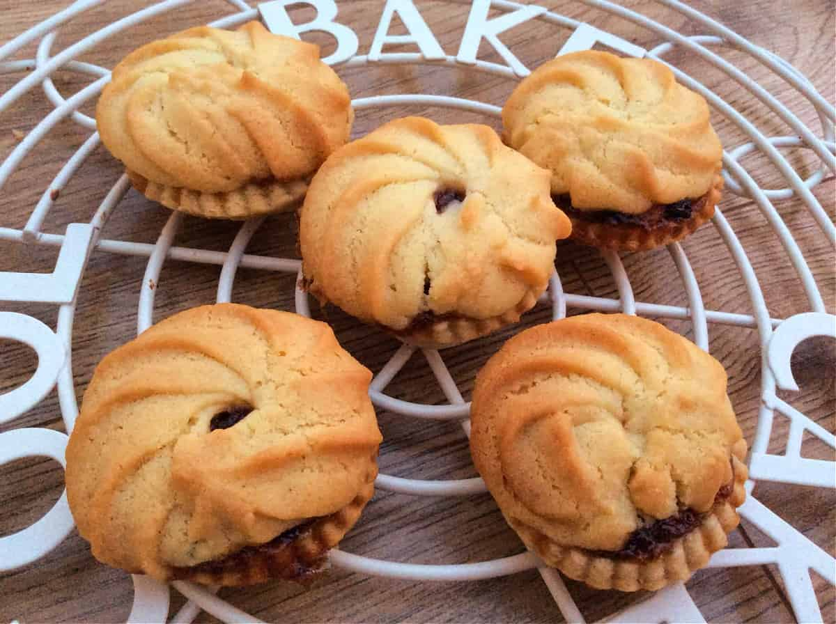 Mince pies with Viennese whirl topping on cooling rack,