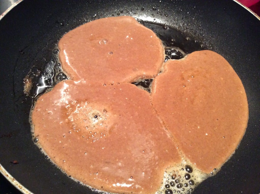 Pancakes cooking in a frying pan.