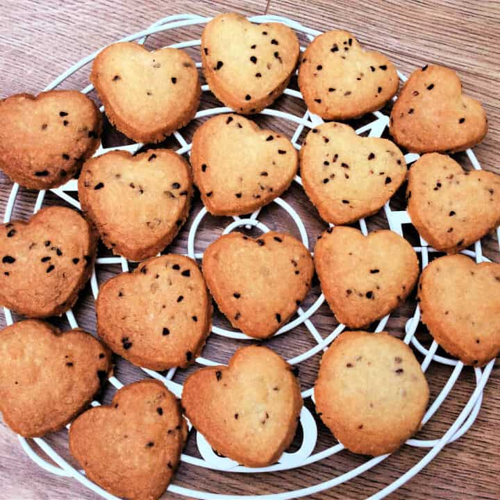 Raspberry shortbread hearts on a white cooling rack.
