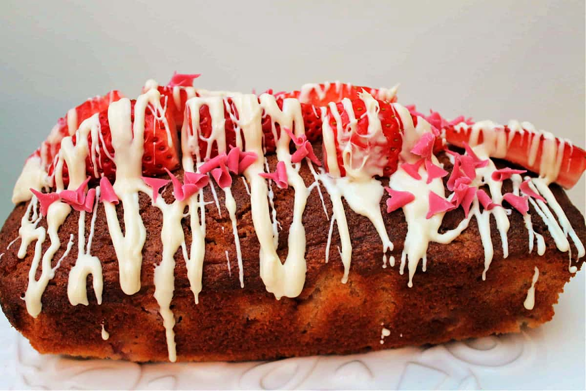 Side view of loaf cake decorated with strawberries and melted white chocolate.