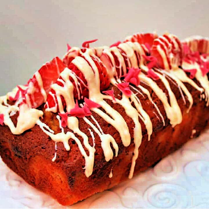 Loaf cake with strawberries and white chocolate drizzled over it.