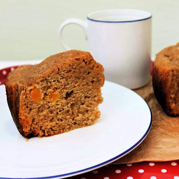 Close up of a slice of apricot cake on a white plate with blue edge, mug of tea in background.