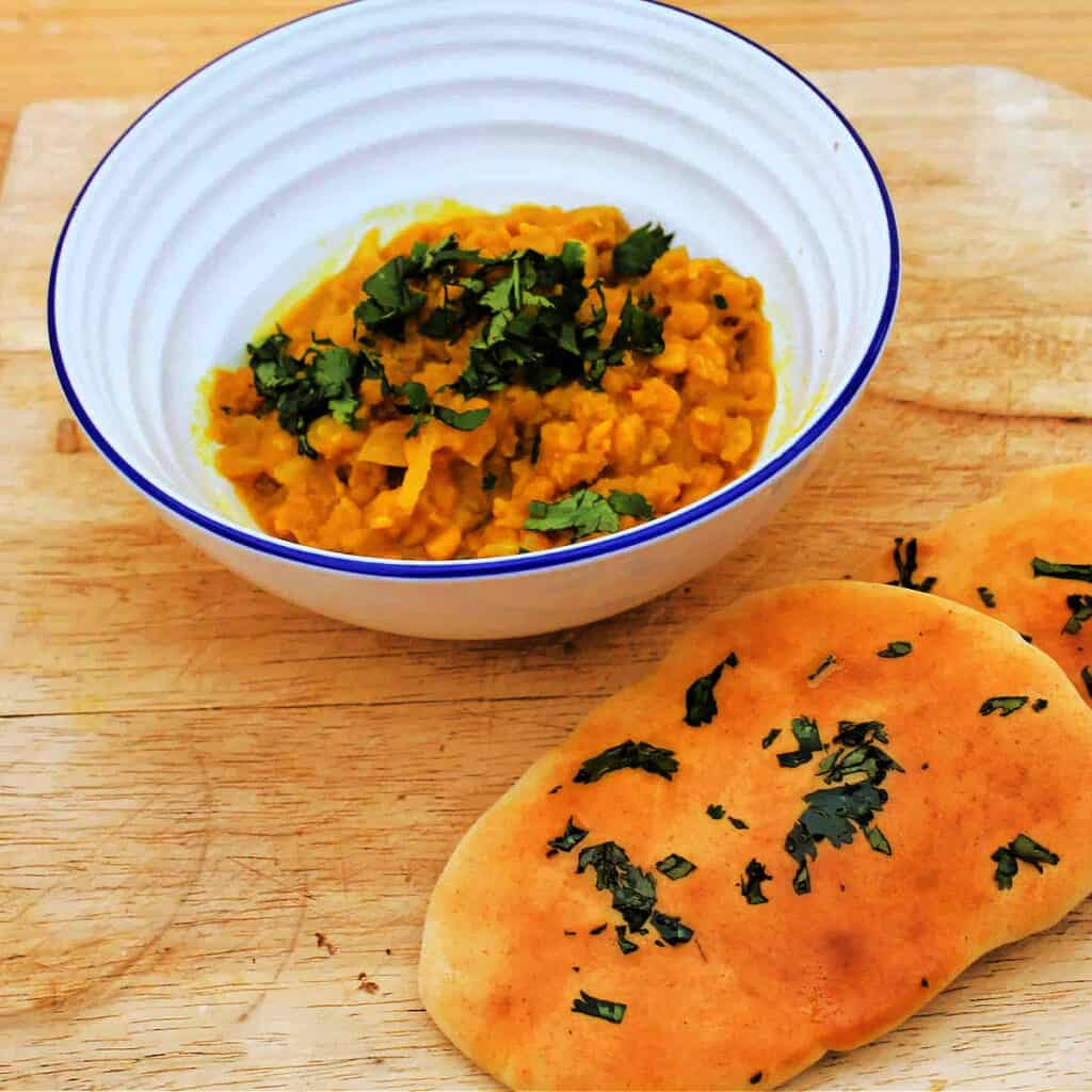 White bowl with yellow dal topped with chopped coriander on wooden board with coriander naan next to it.