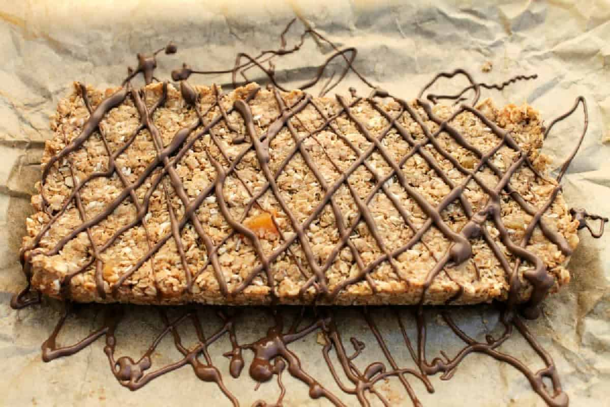 No bake oat bars drizzled with chocolate in a diamond pattern, on baking parchment.