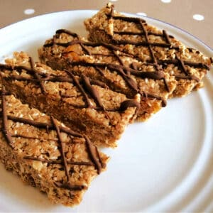Oat bars with chocolate drizzle on a white plate.