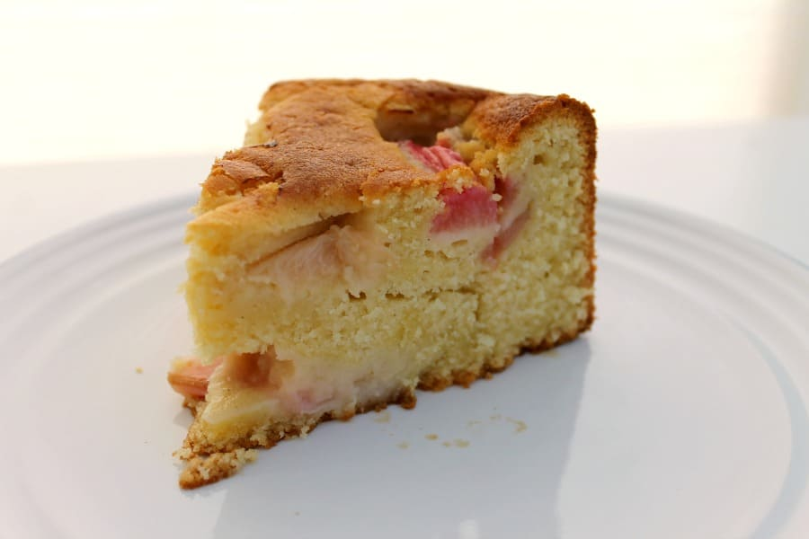 Close up of a cut slice of cake with rhubarb chunks.