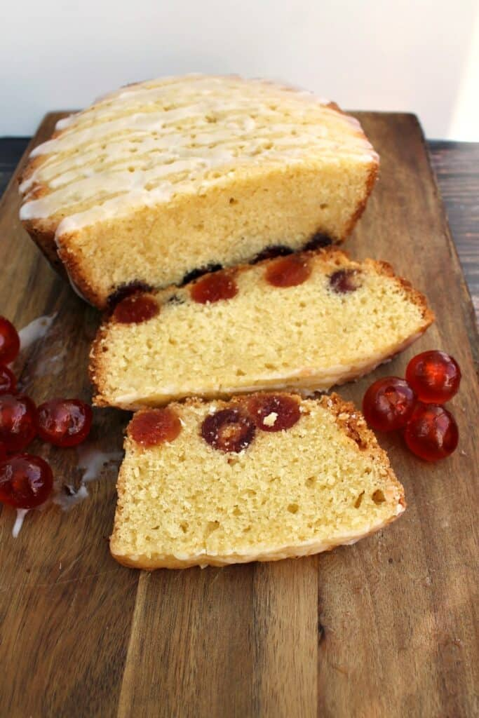 Cherry cake sliced into slices on a board, with cherries around.