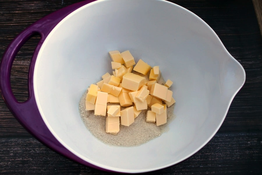 Cubed butter and sugar in a bowl.