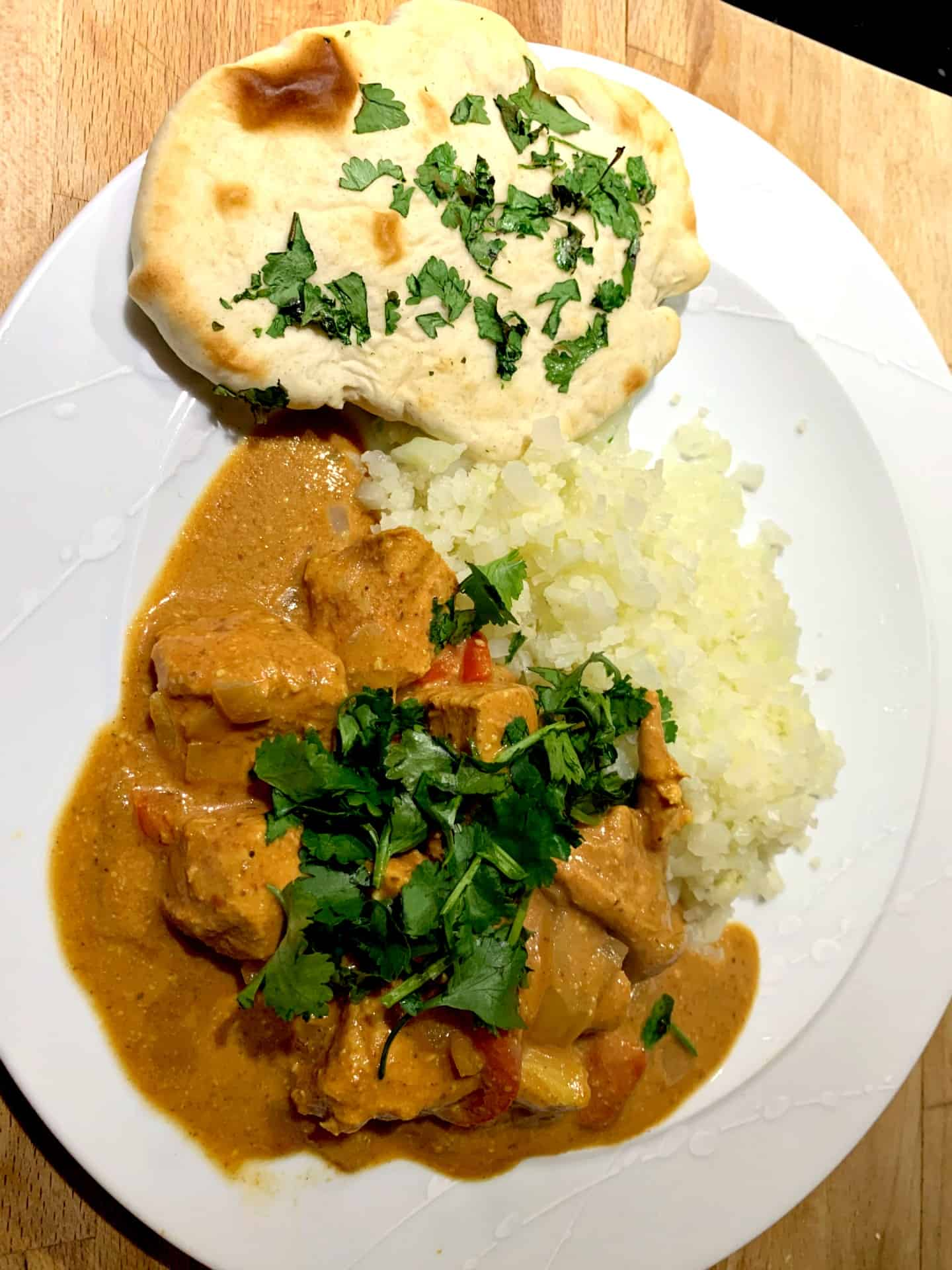Chicken curry on a plate with rice and naan bread.
