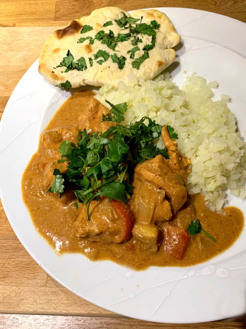 Chicken curry on a plate with rice and a coriander naan, side view.