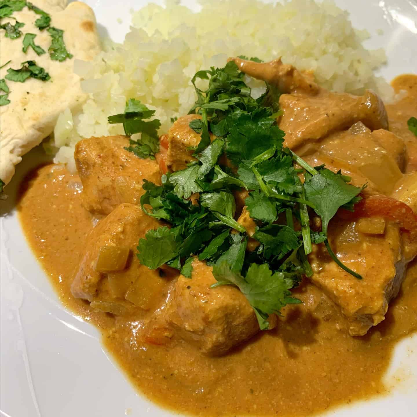 Close-up of chicken curry on a white plate topped with coriander.