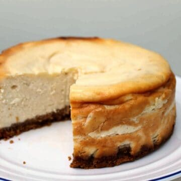 Close up of a cheesecake with a large slice cut out of it, on white plate.