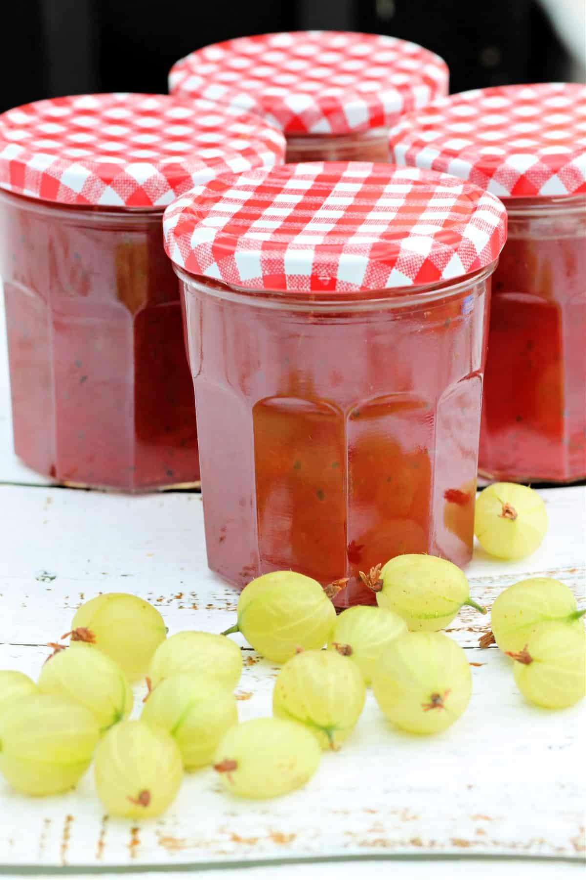 Jars of jam with gooseberries in front.