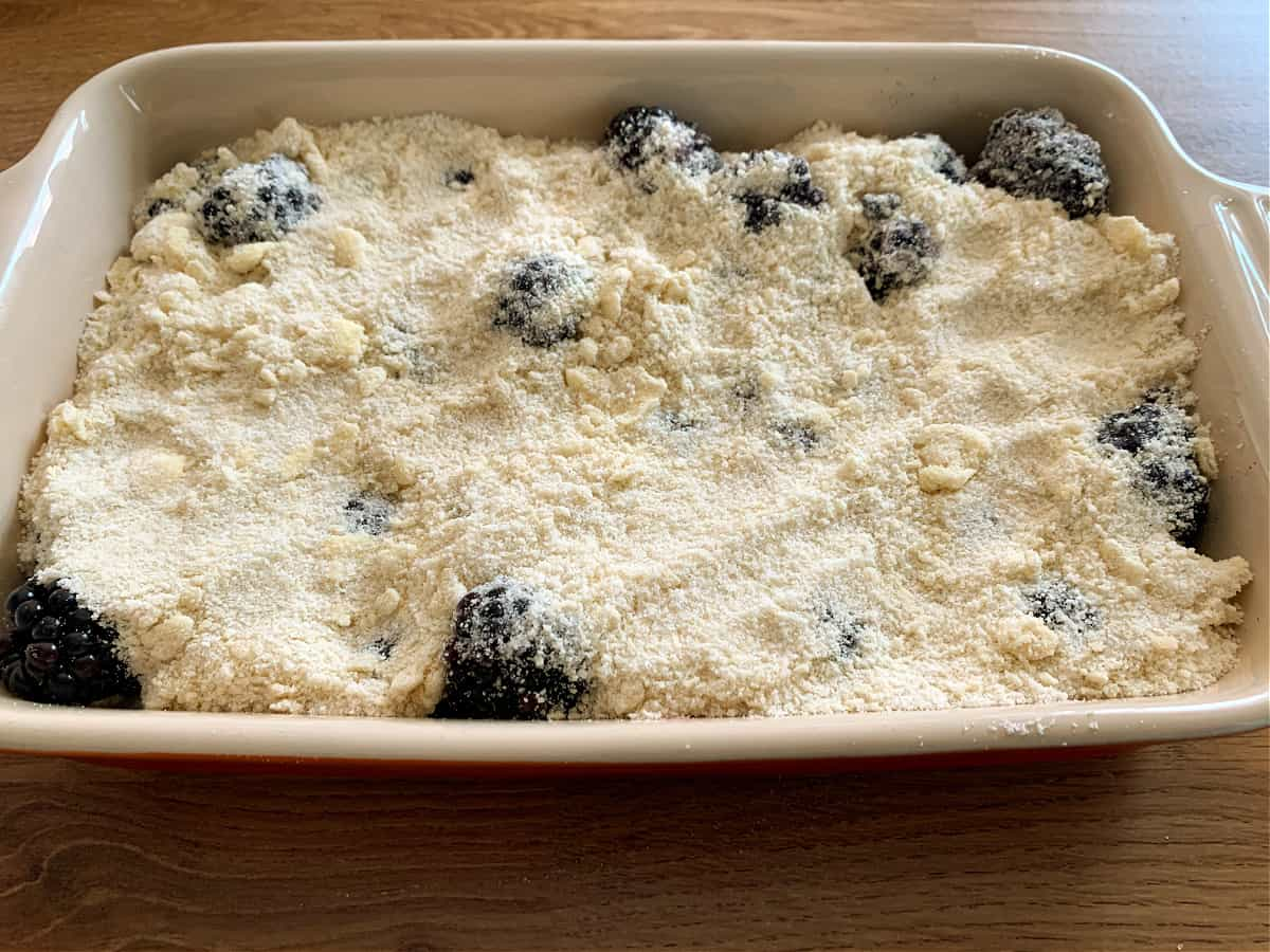 Blackberry crumble in a ceramic dish, before baking.